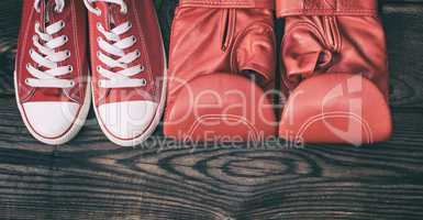 pair of red sneakers and red leather boxing gloves