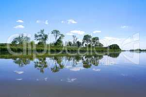 the reflection of the shoreline in the lake, the surface of the lake, calm