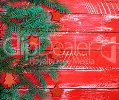 bright red wooden background of boards with green spruce branch