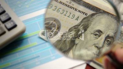 Financial background. Dollar banknote is watched with magnifier.