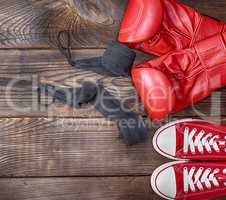 pair of red textile sneakers and red leather boxing gloves
