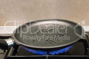 Cast-iron frying pan with ceramic coating is heated on the fire.