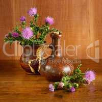 Oil and flowers of milk thistle on wooden .