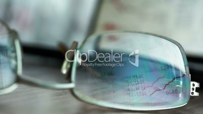 Reflection on glasses of stock market data from computer monitor. Online trading.
