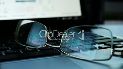 Financial and Business background. Glasses on a keyboard of laptop with Share prices and quotes on a screen.