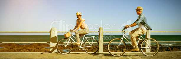Happy couple riding bicycles on pier