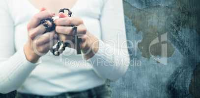 Composite image of midsection of woman holding rosary beads
