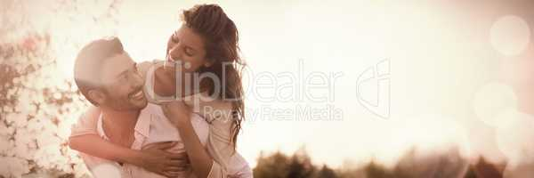 Young man piggybacking woman at farm during sunny day