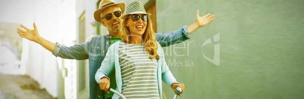 Mature couple riding bicycle by building