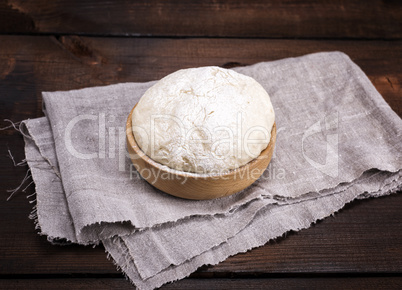 yeast dough in a wooden bowl on a gray napkin