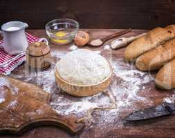 wheat yeast dough for bread and rolls in a wooden bowl