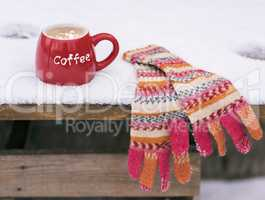 multi-colored knitted mittens and a red cup with coffee