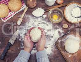 women's hands hold a ball of yeast dough
