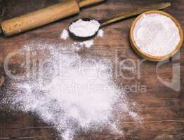 scattered white wheat flour on a brown wooden background