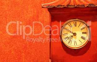 Antique red clock timepiece on a red wallpaper