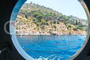 The view from the window of a marine vessel on the stone walls of the old coastal fortress of Alanya