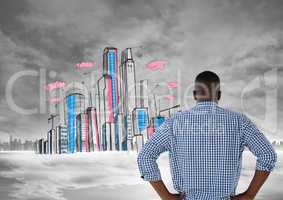 Man looking at doodle of city with city in far background