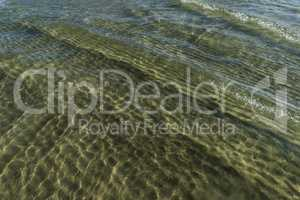Tranquil ocean, ripples and sand.
