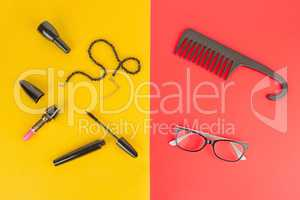 Glasses, cosmetics, jewelry and comb on a yellow and red backgro