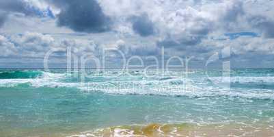 Sandy beach of the tropical ocean and the overcast sky with dram