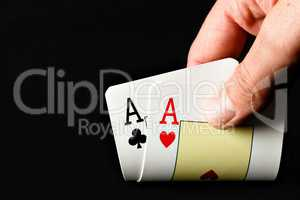 Hand holding two aces.