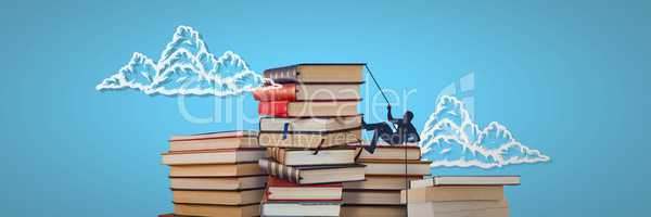 Piles of books with climbing silhouette and clouds on blue background