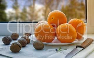Oranges on a plate on the sill of the window.