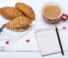 red ceramic mug with hot coffee and fresh croissants