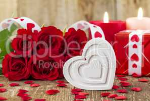 Shape of white heart in front of bouquet of red roses