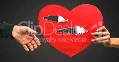 Couple holding hurt love heart with torn paper
