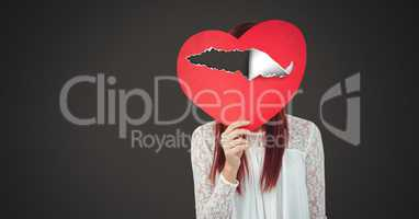 Woman holding hurt love heart with torn paper