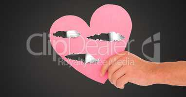 Hand holding hurt love heart with torn paper