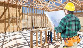 Contractor with hard Hat and Plans Standing Inside Construction