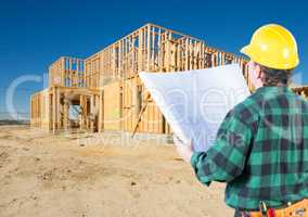Contractor with Plans and Hard Hat Looking At New House Framing