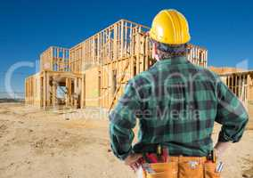 Contractor with Hard Hat Looking At New House Framing at Constru