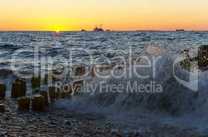sunset on the sea, the waves beat against the breakwater, the sea at dawn, the ships on the horizon