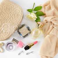 Cosmetics, perfumes, jewelry made of pearls and handbag on a whi