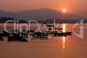 Silhouette of recreational boat, mountain with reflection at sun