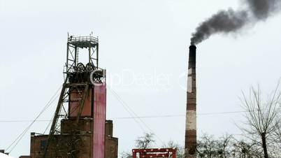 Industrial mine billowing smoke into blue skies