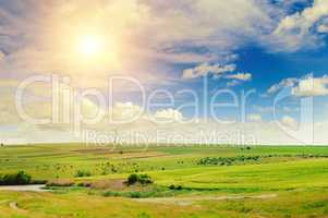 Hilly green field, windmill and sun on blue sky background.