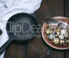 empty round cast-iron frying pan and raw quail eggs in a plate