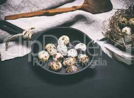 raw quail eggs in the shell lie in a black cast-iron frying pan