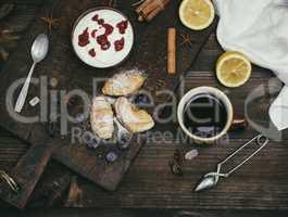a cup of black tea, and yogurt with raspberry jam