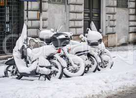 a group of snow-covered scooters