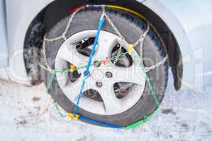 wheel of a car with mounted winter chains