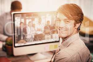 Composite image of happy businessman sitting at computer desk