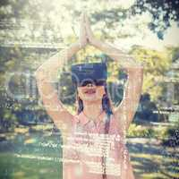 Woman standing with her hands joint while using a VR 3d headset in the park