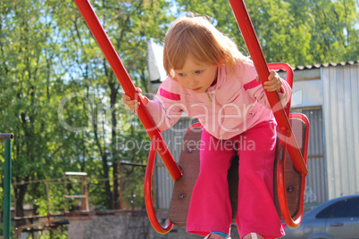 Little girl plays on the swing. Childhood the better years