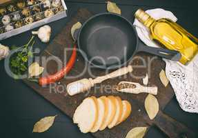 raw quail eggs and an empty round black cast-iron frying pan