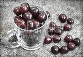 Glass Cup with cherries on the table.